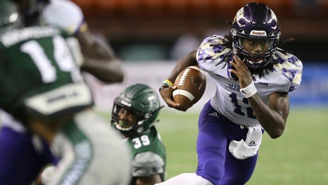 Western Carolina quarterback Tyrie Adams (12) runs through the Hawaii defense during the second quarter of an NCAA college football game, Saturday, Sept. 2, 2017, in Honolulu. (AP Photo/Marco Garcia)