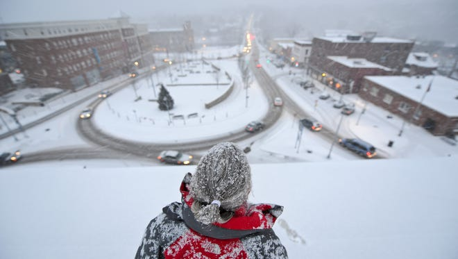 Winooski City Manager Katherine 'Deac' Decarreau on a snowy roof  overlooking the changing landscape of the Winooski rotary in 2010.