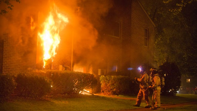 Waupun firefighters wait for water to begin fighting an apartment fire in the 900 block of West Brown Street in the city of Waupun on Thursday night. At least one person was injured in the fire, according to a scanner report.