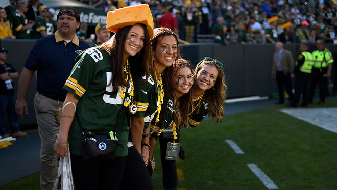 From left, Jessica Waring and sisters Stephanie, Maria and Jamie, all from New York, take a picture along the sideline at Lambeau Field before the Oct. 11 game against the St. Louis Rams. Their father, James Waring, died in the Sept. 11 terrorist attacks and was a die-hard Packers fan.
