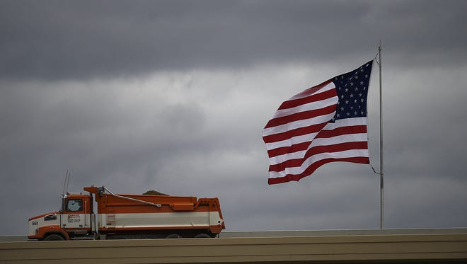 An American flag flaps in the wind as a construction vehicle moves along a flyover ramp to State 29 in Green Bay.