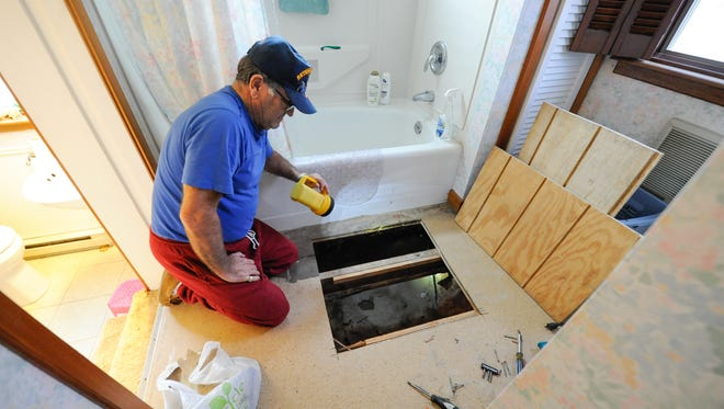 Wilson Coale of Riverdale, near Millsboro, looks at the hole that was cut in his downstairs bathroom, where a water leak in a feed pipe was found and fixed after a previous bill showed a slight increase.