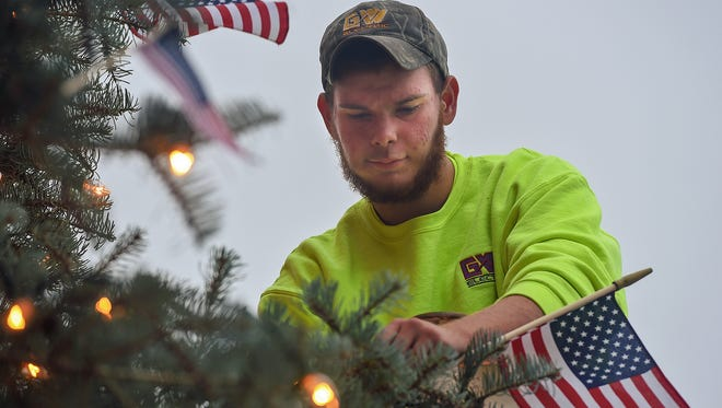 Ben Byers with GW Electric decorates the downtown Christmas tree on Wednesday in Greencastle.  It is the 25th anniversary of decorating the tree in the town square.