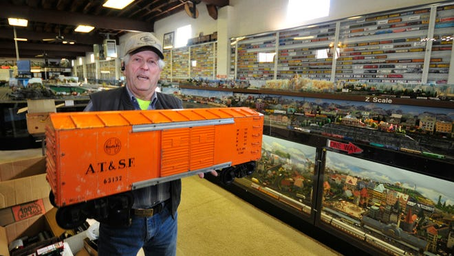 Bill Robinson, vice president of Cumberland Valley Model Railroad, carries one of the larger model trains on display at the Nelson Street location Wednesday, Nov. 25, 2015.