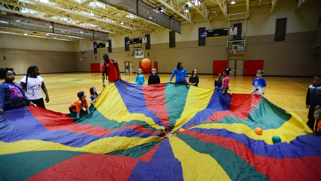 Children participating in the Caine Halter YMCA After School Program play in the gym.
