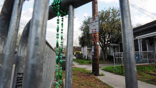 Broken Mardi Gras beads, from a parade gone by, hang on a barricade on East Vermilion Street, Thursday, March 3, 2011, in Lafayette.