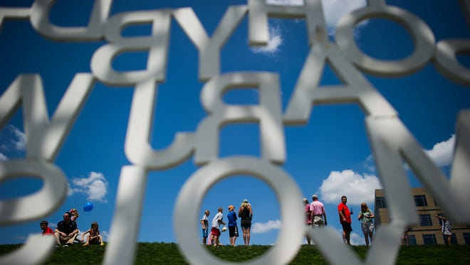 People walk through the Pappajohn sculpture park during the Des Moines Art Festival in Western Gateway Park on Saturday, June 27, 2015.