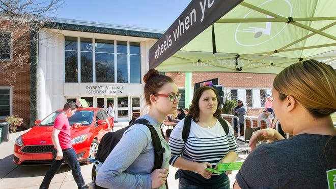 York College students Laura Hegel, left, and Kelly Peck talk with Zipcar representative Christine Chen. Both students plan on using the service.