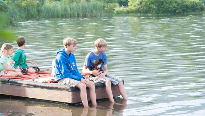 In this 2014 file photo, Bryce and Aidan Spradlin watch the swimming portion of the Enka Triathlon with their puppy,  Scout. The lake is not open to the public.