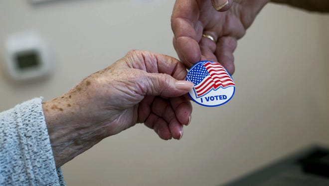 "A poll worker hands a voter an ""I voted"" sticker on May 20, 2014."