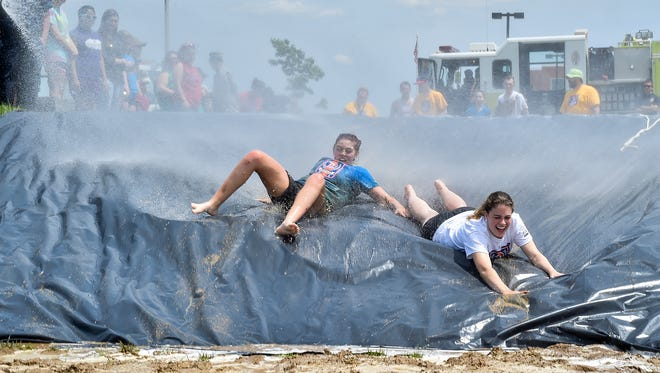 Mara Dean, sophomore and Emily Moyer, junior, are sprayed down with a fire engine hose as they compete in a relay during Color Day at Chambersburg Magnet Career School on Friday, May 20, 2016. The senior class won Color Day.