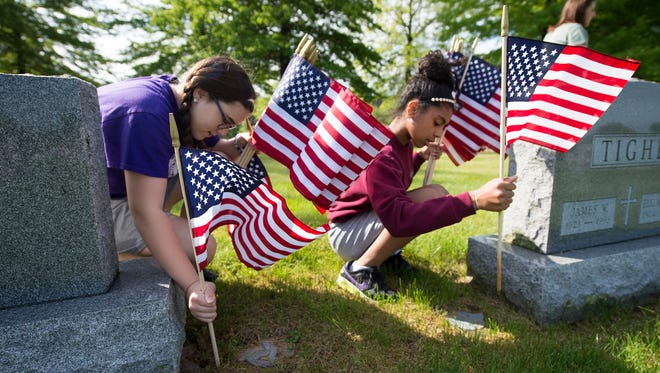 Grace Williams, 11, left, and Selena Spanakis, 11, place flags at the graves of veterans. Students from St. Rose of Lima Elementary School, in Jackson Township, placed flags at Holy Savior Cemetery in Manchester Township for Memorial Day.