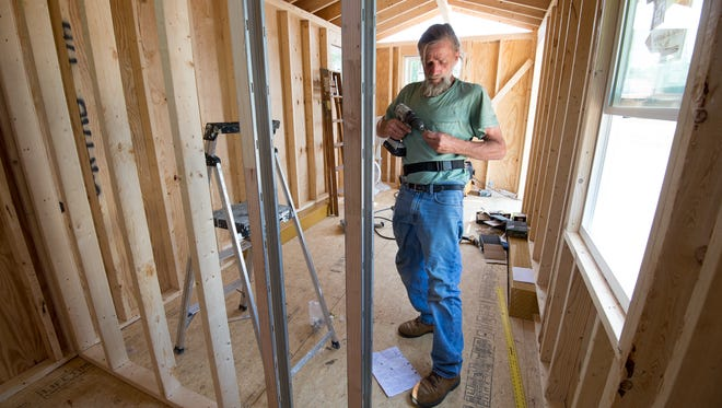 David Wilkins works on installing a pocket door for the bathroom area of a tiny house that they are building for the homeless at Victory Church in Dover.