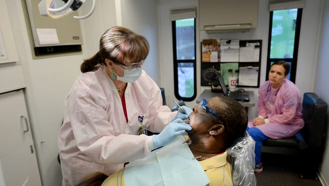 Dr. Dana Parker, left, a dentist with Bon Secours St. Francis mobile dental unit, and Leanna Craft, right, a fourth-year dental student at the Medical University of South Carolina, work on patient James Joyner outside the Triune Mercy Center on Wednesday.