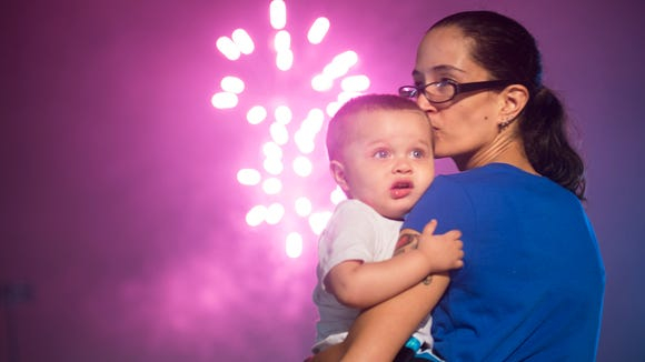 Felicia Benitez comforts her son, Da'Marion Hughes, during his first Fourth of July fireworks show at PeoplesBank Park on July 4, 2016, in York