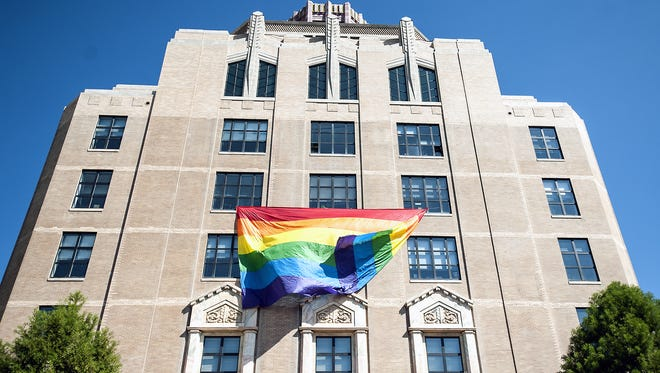 A large rainbow flag hangs from the fourth floor of  Asheville City Hall in October 2014. Councilman Gordon Smith said all seven members of City Council approved hanging the flag as a support for the gay and lesbian members of the community awaiting a court decision on same-sex marriage.
