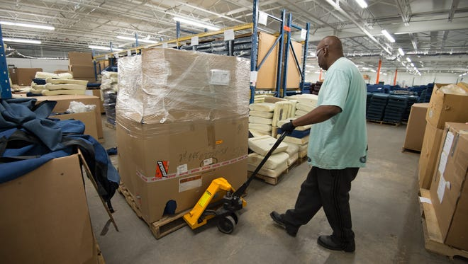 Leonard Barmor moves stacks of seat cushions used on Amtrak trains at First State Manufacturing in Milford.