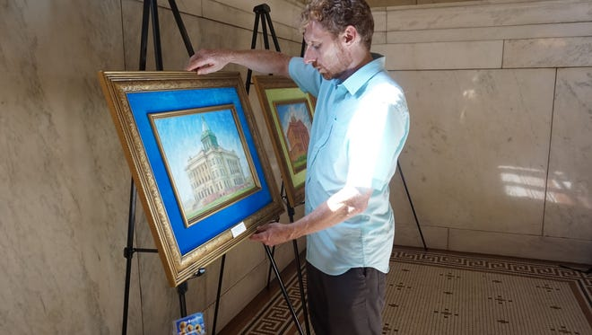 Joseph Doyle, an artist from Madison, sets up a display for his exhibit at the Manitowoc County Courthouse.