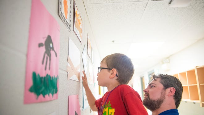 Johnny Wilson, 5, is lifted up by his dad, Matthew Wilson, on Aug. 25, 2016 to touch the piece of art he created during the summer program at the TrueNorth Wellness Services' Amazing Kids Club in Hanover.