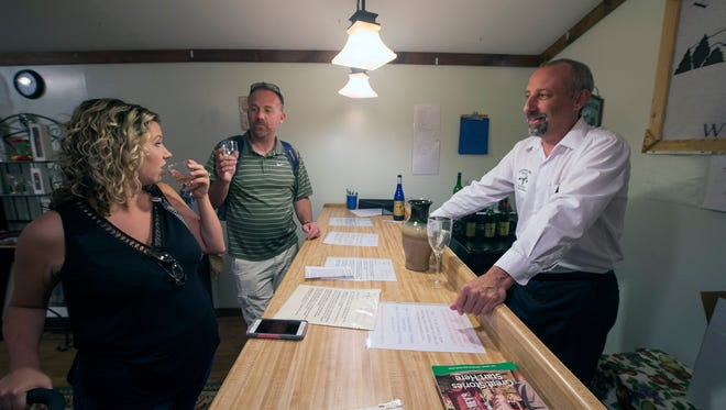 From the left, Jessica and Dave Alley, of Carroll Township, sample wine at Hummingbird Ridge Winery with owner Tom Day.