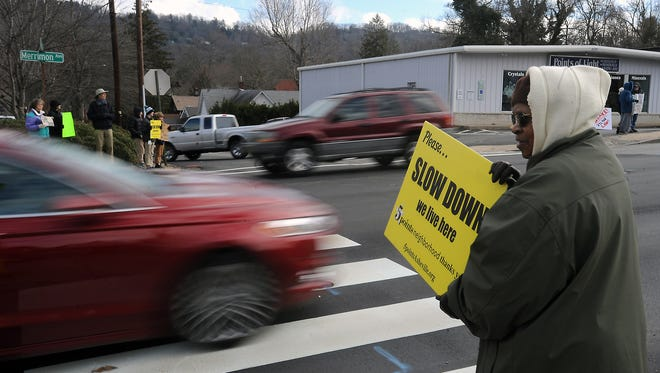 In this 2015 file photo, an Asheville resident holds a sign encouraging drivers on Merrimon Avenue at Coleman Avenue to slow down. The 35 mph speed limit on Merrimon likely will not change.