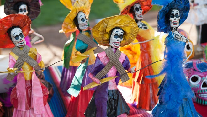 Paper mache Dia de los Muertos dolls on sale at the Dia de los Muertos festival.