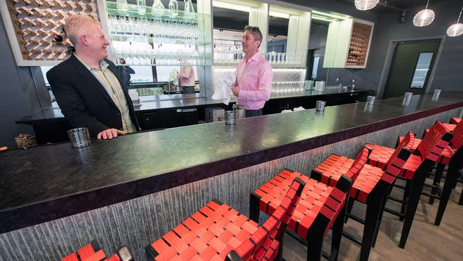 Robert Godfrey, left, and Andrew D'Agenais behind the bar topped in granite and finished in front with a York Wallcoverings product. The bar stools were designed by Peter Danko, at The Handsome Cab in York in January.