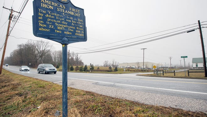 """A historical marker regarding """"America's First Iron Steamboat"""" stands at the intersection of Blessing Road and Lincoln Highway East looking toward  6287 Lincoln Highway, Hellam Township."""
