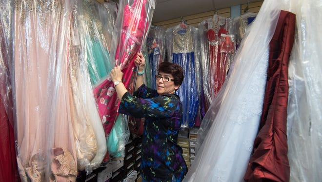 Susan Martinez, owner of Susan's Boutique in Georgetown, helps a custom find a prom dress.