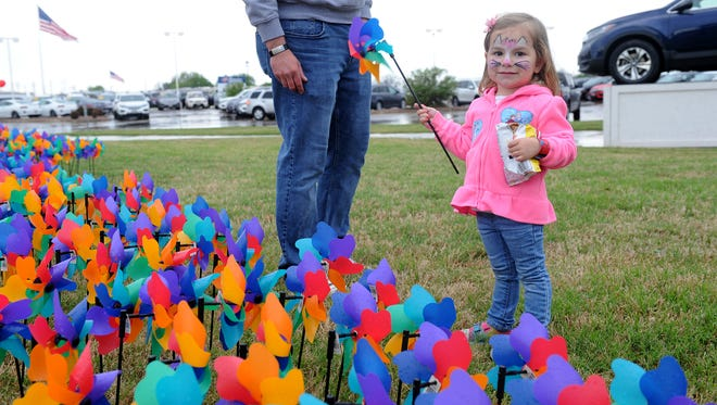Kinsley Biederman, 3, chooses a pinwheel with her dad, Jason, at Pinwheels for Patsy's House. Each pinwheel represents a victim of child abuse in Wichita County.