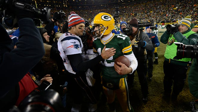 Green Bay Packers quarterback Aaron Rodgers and New England Patriots quarterback Tom Brady exchange words after their 2014 game at Lambeau Field.
