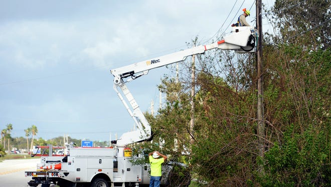 The morning after Hurricane Irma brought high winds and rain to the Treasure Coast, electric crews work on restoring power at the intersection of 37th Street and Indian River Boulevard in Vero Beach, Monday, Sept. 11, 2017.