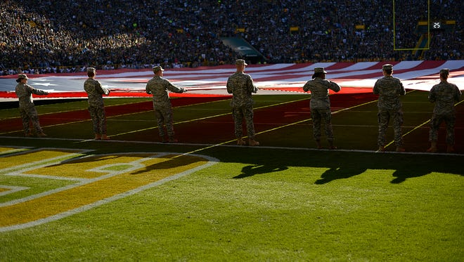 Soldiers take part in holding a large American flag during the playing of the national anthem at Lambeau FIeld in 2016.