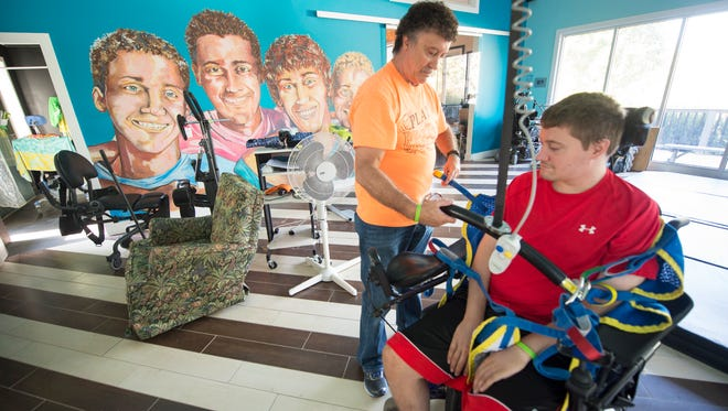 In Brian Keefer's therapy room, Brian's father, Steve, left, positions a lift for Brian. The lift circles most of Brian's living space and can carry him from his therapy room to his bathroom and into his bedroom. The mural on the wall in the background depicts the four Keefer brothers and was painted from a family photograph.
