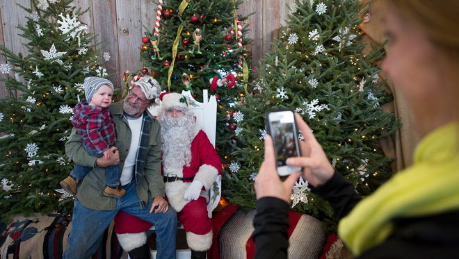 """From the left, eighteen month old Knox feels better about Santa when Knox's grandfather Chris Frazer sits on Santa's lap too. Richard Gibbs, playing Santa Claus, said that he was """"scared to death"""" himself the first time his father took him to see Santa at the Bon-Ton when it was in downtown York at Beaver and Market Streets. Mother Sara Yanavitch, right, takes a picture."""
