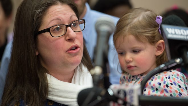Third-grade teacher Lori Sebastian holds her daughter Cora, 2, during a January press conference in support of a bill that will provide 12 weeks of paid family leave to state employees in Delaware.