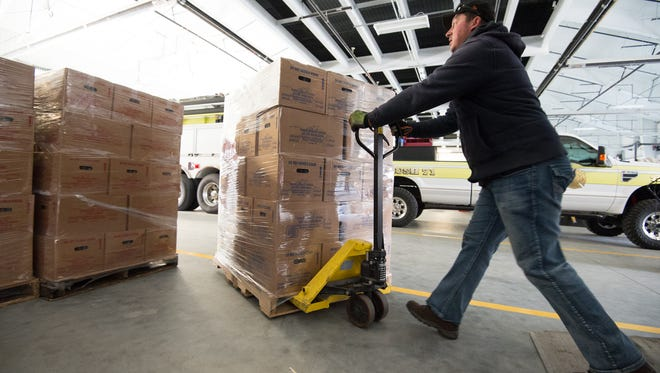 Greg Bromley, operations manager for Eastern Shore Coffee and Water unloads pallets of water at the Blades Volunteer Fire Company.  DNREC and Public Health will be distributing bottled water to Blades residents after they found elevated levels of PFCs in the public drinking water supply.