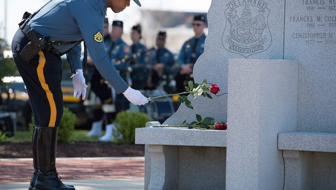 A Trooper places a rose flower on the Troopers Memorial at the Delaware State Police Wreath-Laying Ceremony at the Delaware State Police Headquarters in Dover.