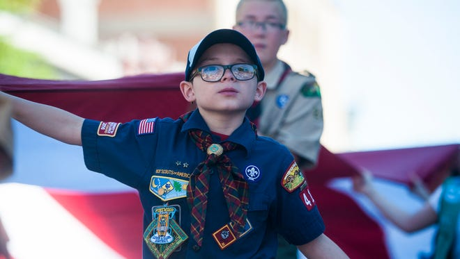 Scouts help hold up an American flag during the Fourth of July parade.
