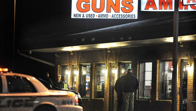 In this Dec. 20, 2012 file photo, law enforcement officials stand outside Riverview Gun Sales, as authorities raid the store in East Windsor, Conn. The shop, which legally sold weapons used in the Newtown school massacre, lost its federal firearms license after the shooting because of hundreds of violations over the past several years, according to federal authorities.