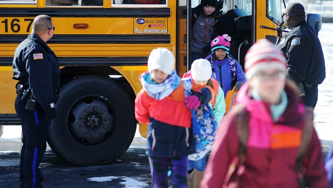 Mark Twain Elementary 4th- and 5th-graders, including 5th-grader Safi Jansma (third from right), 10, get off a bus at a secret location during an emergency reunification drill on Tuesday, Nov. 18, 2014, in Sioux Falls, S.D. Mark Twain Elementary School 4th- and 5th-graders and their teachers participated in the drill with emergency personnel, which simulated an explosion in the school, where they were evacuated, transported to a secret location and reunited with their parents.