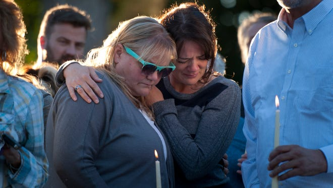 In this photo taken on Thursday, Oct. 2, 2014, family and friends console one each other while people speak and tell stories during a vigil for the Strack family at Pioneer Park in Provo, Utah. More than 100 family members and friends gathered to remember five members of the family mysteriously found dead at home last weekend.