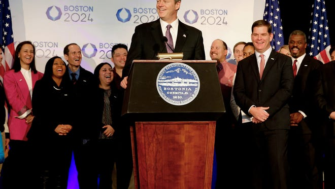 FILE - In this Jan. 9, 2015, file photo,  Massachusetts Gov. Charlie Baker speaks during a news conference in Boston, as Boston Mayor Martin Walsh, second from right, and other looks on, after Boston was picked by the USOC as its bid city for the 2024 Olympic Summer Games. The leaders of the U.S. Olympic Committee are supposed to hear from the governor of Massachusetts on Monday, July 27, 2015. What he tells them could very well dictate the future of Boston's bid for the 2024 Olympics.