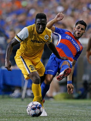 FC Cincinnati midfielder Emmanuel Ledesma (45) is pushed over by Nashville SC midfielder Bolu Akinyode (30) chasing the ball in the first half of the USL soccer match between the FC Cincinnati and the Nashville SC at Nippert Stadium in Cincinnati on Saturday, Aug. 4, 2018. FC Cincinnati led 1-0 at halftime.