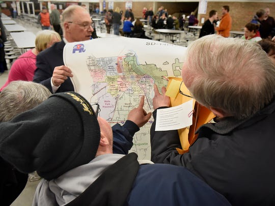 In this 2016 file photo, voters look for their addresses on a precinct map during the Senate District 14 Republican Caucus at Apollo High School in St. Cloud.