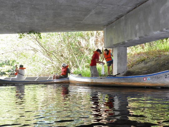 The Bejarano family collects trash by canoe from beneath the US 41 overpass along the Estero River as part of National Public Lands Day Sept. 24.