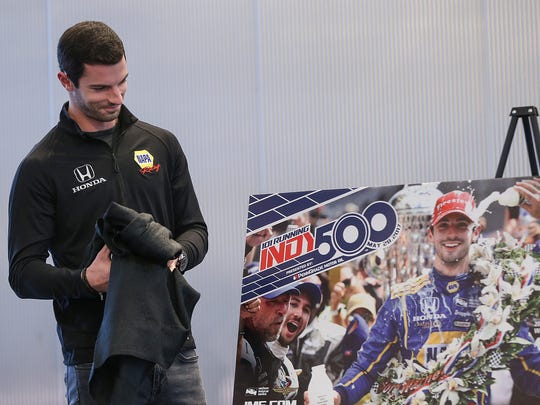 At left, Indianapolis 500 winner Alexander Rossi smiles as he sees himself on the 2017 ticket design for the 101st Indianapolis 500, at Cummins distribution headquarters on East Market Street in downtown Indianapolis, Thursday, Feb. 16, 2017. The ticket design unveiling kicked off the 100-day countdown to the 101st Indianapolis 500.