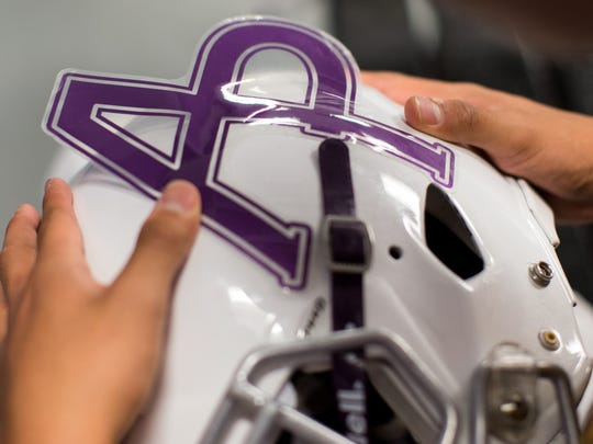 Aransas Pass's Jonathan Trevino places a AP sticker on his helmet as he waits in the varsity locker room in the teams field house to leave for their game against Taft in Portland on Friday, Sept. 15, 2017.