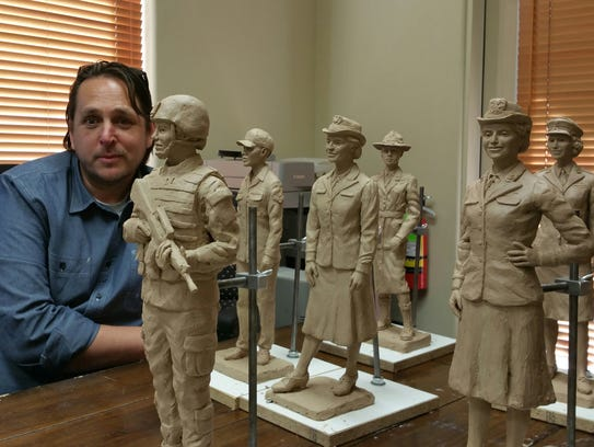 Sculptor Matt Glenn poses with some of his maquettes.