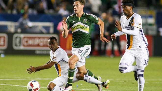 Portland Timbers forward Lucas Melano, center, moves the ball away from Los Angeles Galaxy defender Ashley Cole, left, and forward Bradford Jamieson IV during the second half of an MLS soccer game in Carson, Calif., Sunday, April 10, 2016. The game ended in a 1-1 draw. (AP Photo/Ringo H.W. Chiu)